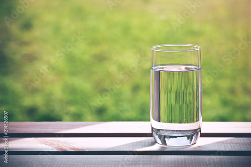 Fotografia Glass of pure water on green natural background. Space for text