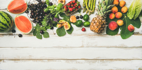 Summer food background. Flat-lay of seasonal fruit, vegetables and greens over white wooden background, top view, copy space. Vegetarian, vegan, dieting, clean eating ingredients