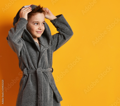 Fotografie, Obraz  Boy kid standing in gray bathrobe looking at the corner on yellow