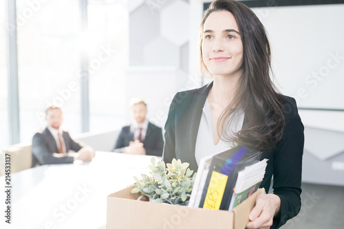 Waist up portrait of smiling young businesswoman holding box of personal belongi Canvas