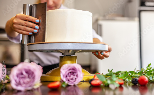 Valokuvatapetti The chef's confectioner cooks a cake and decorates it with fresh flowers