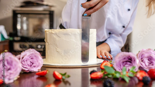 Fényképezés  The chef's confectioner cooks a cake and decorates it with fresh flowers