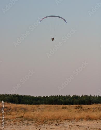 Fototapeta Motolotniarz w powietrzu, na ziemi piaszczysty teren, suche trawy i linia lasu obraz