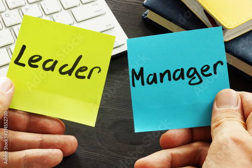 Photo  Leader vs manager. Man is holding memo sticks.