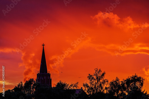Tuinposter Rood sun-dominated church towers with colorful skies