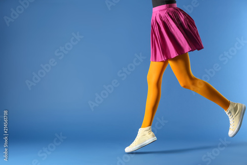 Obraz na plátně Legs of beautiful young woman wearing tights and skirt on color background