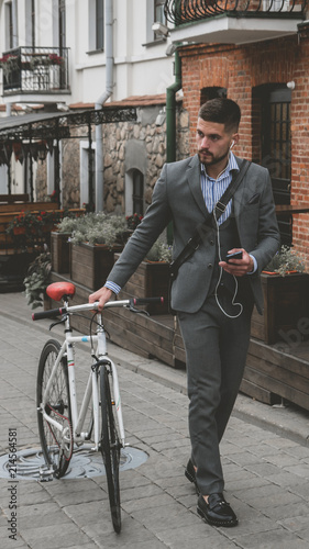 In de dag Fiets Handsome young adult man wearing suit choosing music on his phonee before riding his classic bicycle to work in the morning