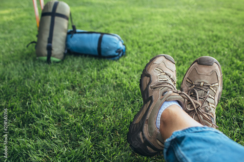 Fotografija  Selfie of legs in trekking shoes on green grass near equipment for hiking and tr