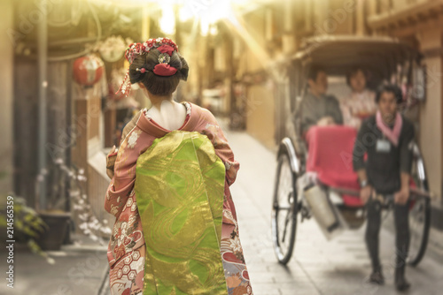 Valokuva Maiko walking in an alley of Kyoto in the sunset light crossing a rickshaw