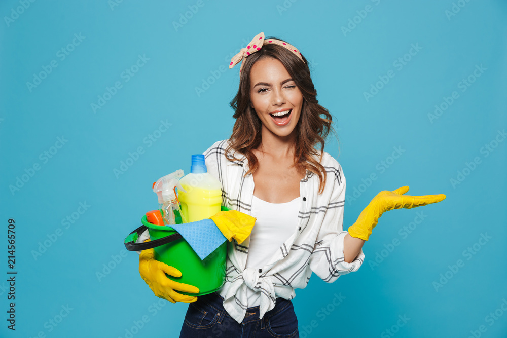 Fototapety, obrazy: Portrait of smiling happy housewife 20s wearing yellow rubber gloves for hands protection holding bucket with cleaning supplies, isolated over blue background