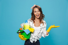 Portrait Of Smiling Happy Housewife 20s Wearing Yellow Rubber Gloves For Hands Protection Holding Bucket With Cleaning Supplies, Isolated Over Blue Background