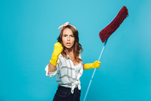 Portrait Of Strong Young Housewife 20s In Yellow Rubber Gloves Holding Mop During Cleaning And Showing Fist At Camera, Isolated Over Blue Background