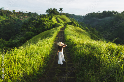 Canvas-taulu Young beautiful woman walking on Campuhan Ridge way of artists, in Bali, Ubud