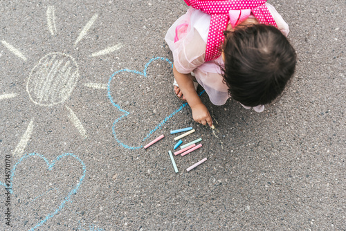 Foto Top view image of happy little girl wears pink dress and backpack drawing with colorful chalks on the sidewalk