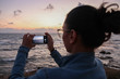 A young woman photographs with her smart phone a sunset at sea
