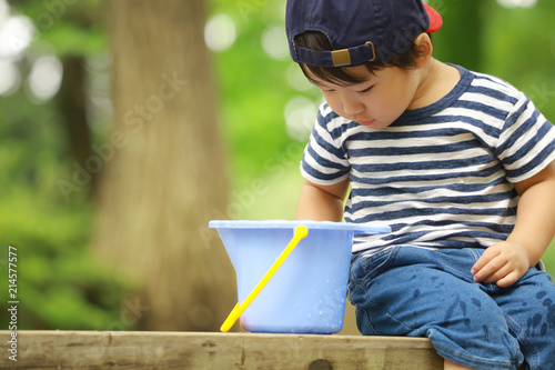 Fotografie, Obraz  バケツの中を見る男の子