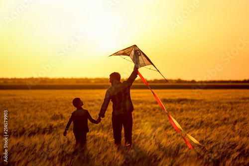 Fotografiet  Happy father and son flying kite in the field at sunset