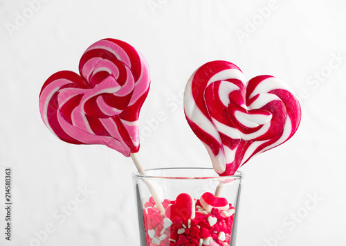 Fototapeta Glass with tasty heart-shaped lollipops and candies on white background