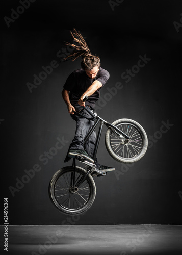 Foto A man doing an extreme stunt on his BMX bicycle.