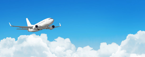 Passenger aircraft cloudscape with white airplane is flying in the daytime sky cumulus clouds, panorama view.