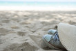 Sneakers with straw hat on beach. Summer accessories concept.