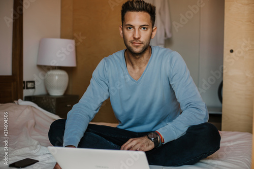 Working moments at home.Happy caucasian coworker man in casual clothes working on laptop at modern apartment. Blurred background