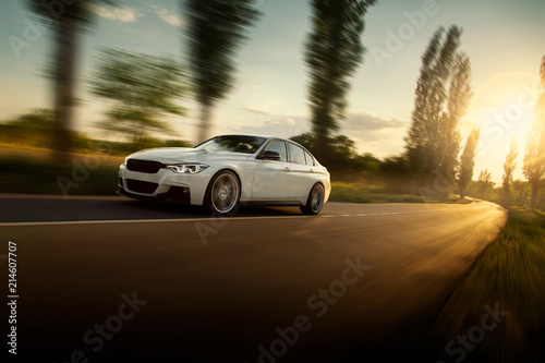 White car is driving on empty countryside asphalt road at sunset