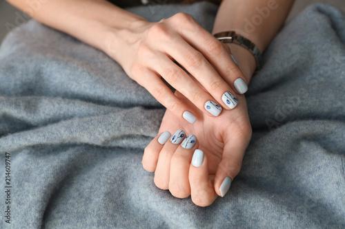 Fotografía  Young woman showing beautiful manicure on blanket, closeup
