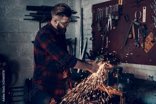 Vászonkép Young Bearded Mechanic Repairing Parts in Garage.