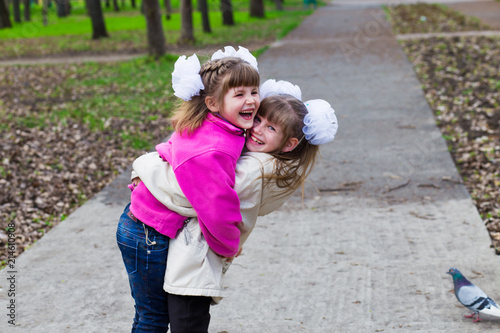 two funny siblings sister hugging with each other while walk in park