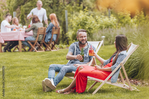 Smiling friends cheering during meeting while relaxing on sunbeds in the garden Poster Mural XXL