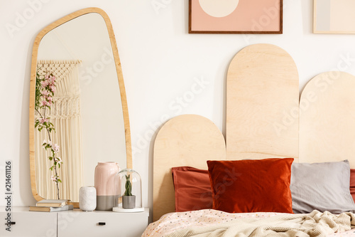 Fotografia Red cushions on bed with headboard next to dressing table with mirror in bedroom interior