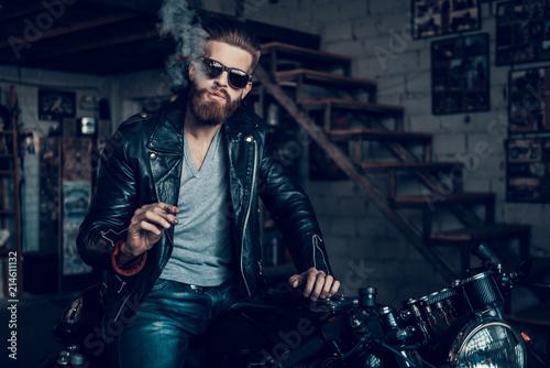 Fotografía  Young Bearded Biker in Sunglasses Smoke Cigar.
