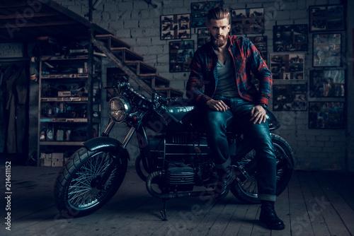 Fototapeta Bearded Biker Sitting on Motorcycle in Garage. obraz