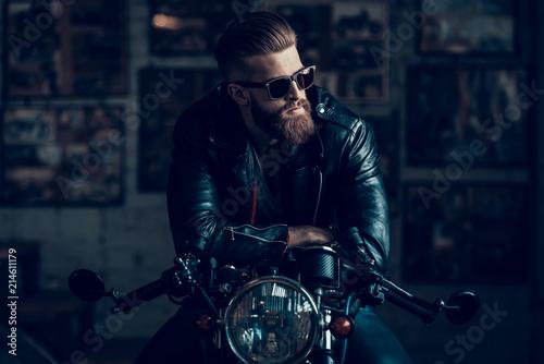Fotografia, Obraz Young Biker in Sunglasses on Motorcycle in Garage.