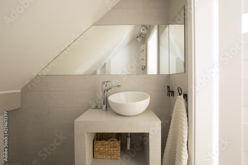 Obraz Mirror above washbasin in beige bathroom interior on attic with towel. Real photo - fototapety do salonu