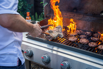 Čovjek koji u vrtu Ujedinjenog Kraljevstva kuha roštilj s plamenom