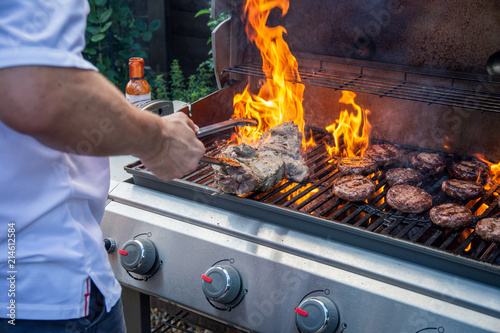 Fototapeta Man cooking barbecue with flames in a UK garden obraz