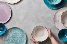 Female Hands Hold A White Ceramic Bowl On A Gray Marble Table. Clay Handcraft Bowls, Plates Of Different Sizes Are Empty.