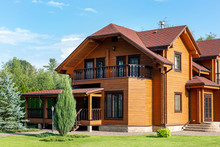 Beautiful Luxury Big Wooden House. Timber Cottage Villa With With Green Lawn, Garden And Blue Sky On Background
