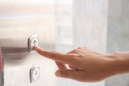 Close up waman hand press a up button of elevator inside the building for upper high level floor Canvas Print