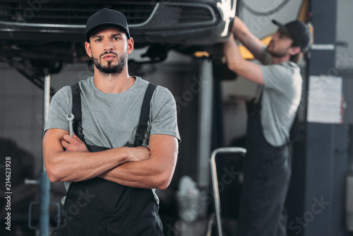 serious mechanic with crossed arms holding wrench, while colleague working in workshop behind