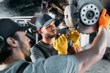Professional Amle Mechanics Repairing Car Without Wheel In Auto Repair Shop