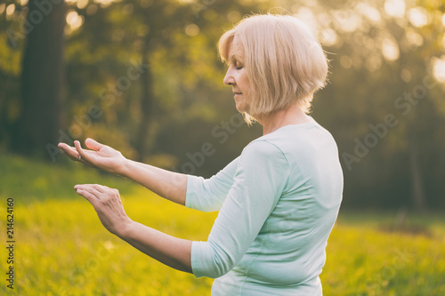 Senior woman enjoys  exercise Tai Chi in the nature.