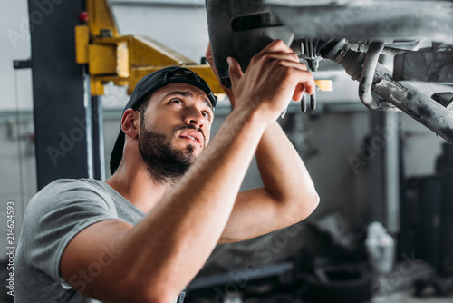 Fotografia  professional technician repairing car in mechanic shop