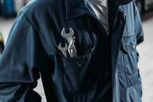 Cropped View Of Workman In Overalls With Wrenches In Pocket