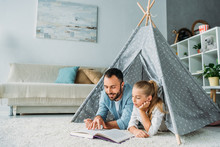 Father And Daughter Lying On Floor Inside Of Teepee And Reading Book Together At Home