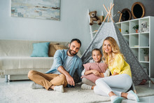 Happy Young Family Sitting On Floor With Teepee And Looking At Camera