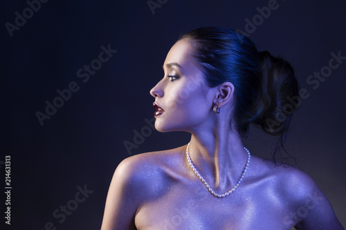 Fotografia Beautiful brunette girl with naked shoulders and dark red lips make-up, wearing earrings and a pearl necklace, illuminated in blue