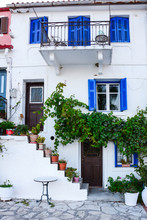 A White Facade On Old Greek Houses With Blue Doors, Windows In The Afternoon Delights Tourists From All Over The World. A Staircase With Various Flowerpots And Flowers.